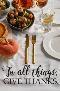 baked potatoes, glasses with white rose and lemon water and cutlery on white tablecloth with in all things give thanks illustration