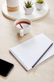 zöld növények, csésze tea és üres notebook ceruza közelében okostelefon fa felületen
