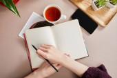 kivágott kilátás nő írás notebook közelében zöld növények fa fórumon, csésze tea, okostelefon bézs felületen