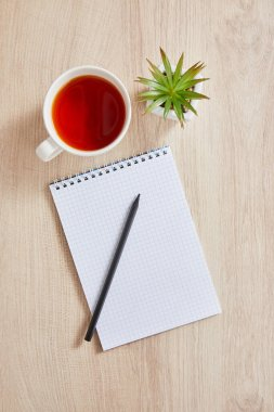 Top view of green plant, cup of tea and blank notebook with pencil on wooden surface stock vector