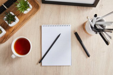 Top view of green plants, cup of tea and blank notebook with pencils and pens on wooden surface stock vector