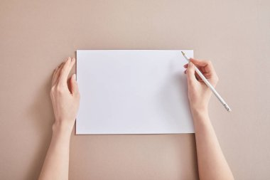 Cropped view of woman writing on paper with pencil on beige surface stock vector
