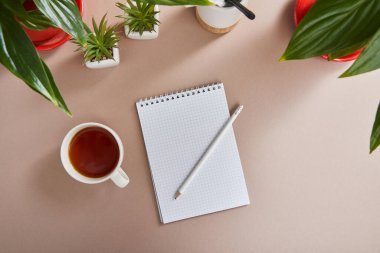 Top view of green plants, cup of tea, blank notebook with pencil on beige surface stock vector