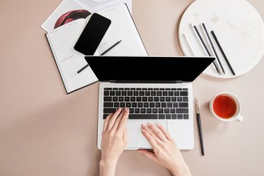 Cropped view of woman using laptop near cup of tea, planner, smartphone near circle with pencils on beige surface stock vector