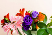 Photo floral composition with bouquet of colorful flowers isolated on beige, selective focus