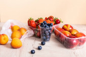 fruit composition with blueberries, strawberries, nectarines and peaches in plastic containers on wooden surface isolated on beige