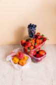 ovocné složení s borůvkami, jahodami, nektarinkami a broskvemi v plastových nádobách na dřevěném povrchu na béžovém pozadí