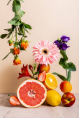 floral and fruit composition with roses, Eustoma, gerbera, Alstroemeria, citrus fruits, strawberries and peaches on beige background