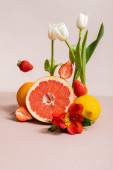 floral and fruit composition with tulips, red Alstroemeria, summer fruits isolated on beige