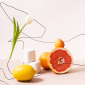 floral and fruit composition with tulip on wire and fruits on cubes isolated on beige