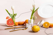 floral and fruit composition with tulips, fruits, dishware isolated on beige