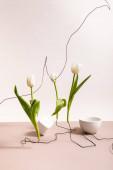 kreativní květinová kompozice s tulipány na drátech, pohár a čtvercová krychle izolované na béžové