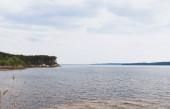 modré a čisté jezero v blízkosti zelených stromů proti obloze s mraky