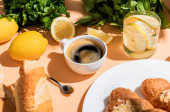 káva, čerstvé croissanty a voda k snídani na béžovém stole