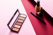 make-up nadace, oční stíny, kosmetický štětec a rtěnka na růžové a karmínové