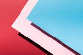 horní pohled na prázdné růžové a modré papírové listy na karmínovém
