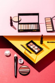 eye shadow palettes near cosmetic brushes, lipsticks and face powder on crimson, pink and yellow