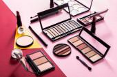 oční stíny palety a kosmetické štětce v blízkosti rtěnky a pudr na obličej na karmínové, růžové a žluté