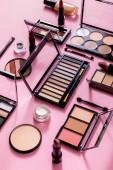 ruměnec a oční stíny palety v blízkosti kosmetických štětců, obličejové základy a rtěnky na růžové