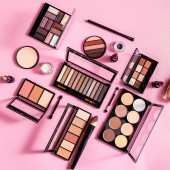 top view of blush and eye shadow palettes near cosmetic brushes and lipsticks on pink