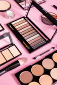szemhéjpúder és pirosító paletta kozmetikai kefék és arcpúder közelében rózsaszínen