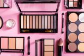 horní pohled na oční stíny a zarudlé palety v blízkosti kosmetických kartáčů na růžové