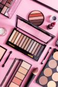 horní pohled na rtěnku, kosmetické štětce a zarudnutí v blízkosti oční stíny palety na růžové