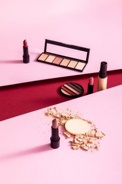 Makeup foundation, eyeshadow palettes and lipsticks near cracked face powder on pink and crimson stock vector
