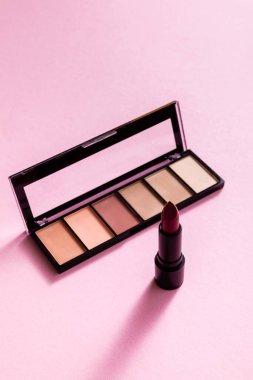 Eye shadow palette near lipstick on pink stock vector