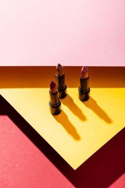 Shadows near lipsticks on yellow, crimson and pink stock vector