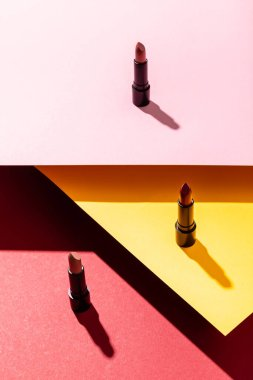 Shadows near lipsticks on crimson, yellow and pink stock vector