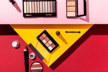 Top view of eye shadow palettes and cosmetic brushes near lipstick on crimson, pink and yellow stock vector