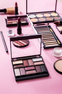 Eye shadow and blush palettes near face powder, cosmetic brushes, face foundation and lipsticks on pink stock vector