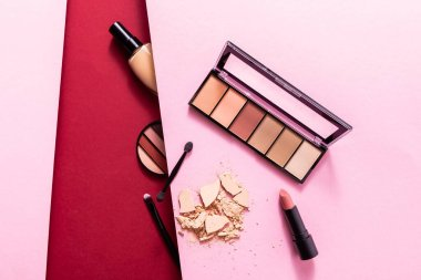Top view of face foundation near eye shadow palette, cracked face powder, cosmetic brushes and lipstick on pink and crimson stock vector