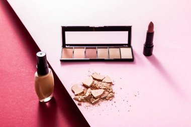 Face foundation near eye shadow palette, cracked face powder and lipstick on pink and crimson stock vector