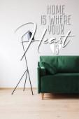 zelená pohovka s polštářem v blízkosti moderní podlahové lampy a doma je místo, kde vaše srdce je nápis