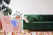 moderní zelená pohovka a polštáře v obývacím pokoji s barevným kobercem v blízkosti kresleného křesla a rostlin ilustrace