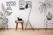 Photo floor lamp, wooden coffee table and clock with blank screen near drawn plants, paintings and dresser