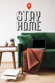 zelená pohovka s dekou a notebookem v blízkosti dřevěného konferenčního stolku a zůstat doma nápisy