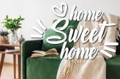 zöld kanapé, párna, könyv és takaró a fa dohányzóasztal mellett, növényekkel és otthon édes felirattal