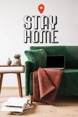 Green sofa with blanket and laptop near wooden coffee table and stay home lettering stock vector