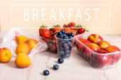 blueberries, strawberries, nectarines and peaches in plastic containers on wooden surface near breakfast lettering on beige