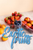 blueberries, strawberries, nectarines and peaches in plastic containers near exotic fruits lettering on beige