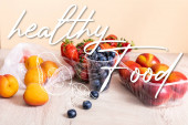 blueberries, strawberries, nectarines and peaches in plastic containers on wooden surface near healthy food lettering and avocado illustration on beige
