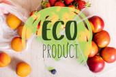 top view of fruit composition with blueberries, strawberries and nectarines in plastic containers near eco product lettering on wooden surface