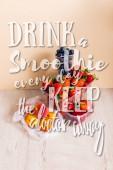 fruit composition with blueberries, strawberries, nectarines and peaches in plastic containers near drink a smoothie every day keep the doctor away lettering on beige