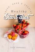 fruit composition with blueberries, strawberries, nectarines and peaches in plastic containers near start diet lettering on beige