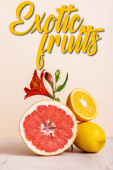 floral and fruit composition with red Alstroemeria and citrus fruits near exotic fruits lettering on beige