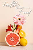 floral and fruit composition with citrus fruits, strawberry and peach near healthy food lettering on beige