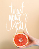 cropped view of female hand with juicy grapefruit half near trust your soul lettering on beige